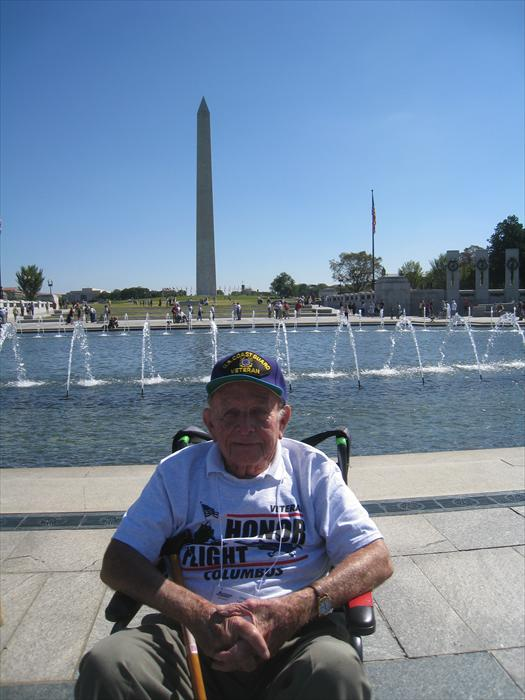 WW II Hero Bob Lamp at the World War II Memorial with the Washington Monument in the background.