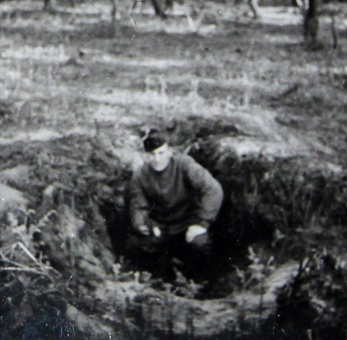 Picture taken after the war when Walter went back to a fox hole he had slept in during a battle.