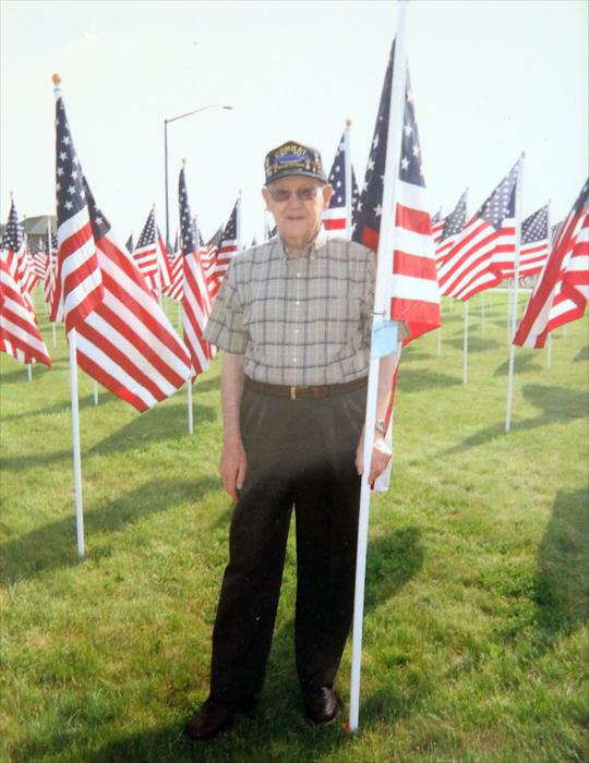 Picture of Walter standing in front of the flag of heroes in Westerville, Ohio.