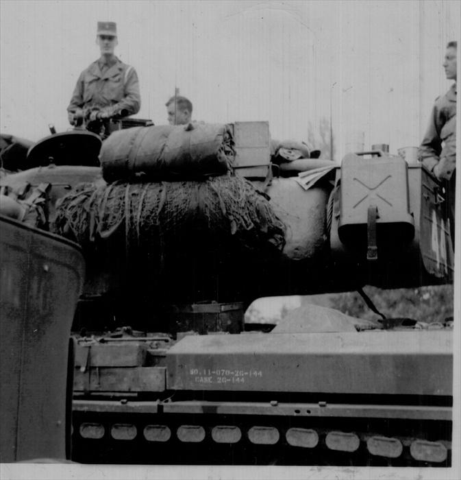 John Tubinis, PFC, 1st ID HQ CO, standing in the turret of a M-34 tank carrying a 50-cal. machine gun.  A warm weather maneuver.  Dad umpired as indicated by the white engineer's tape around his left shoulder.  Germany 1951-1953.