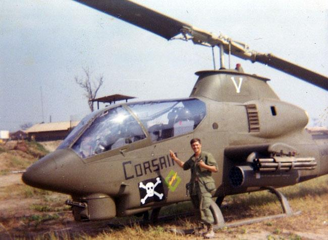 Eldon standing in front of a Cobra Corsair helicopter in Vietnam.