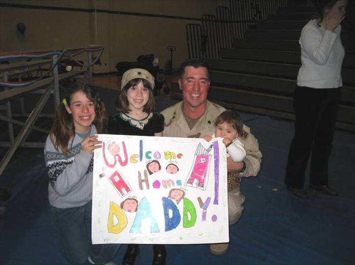 Picture of me and my girls with the 'Welcome Home Daddy' sign they made just for me!  March 2005.
