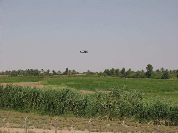 Picture of an AH-64 Apache helicopter flying by the EECP above the farmland that surrounded our base.