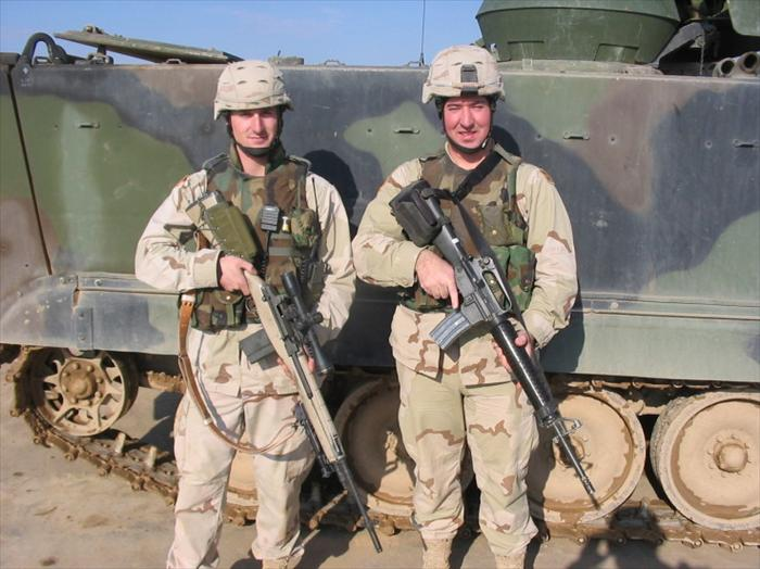 Picture of Specialist Jeffrey Dickerson (our 'Designated Marksman' or DM) holding a modified M14 rifle and myself cheezin' for the camera.
