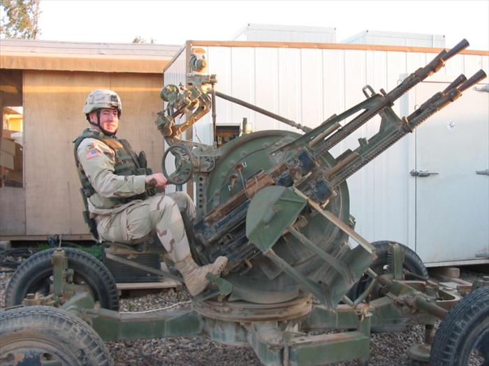 Photo op; me sitting on an old Russian-made, quad machine guns-AAA (Anti Aircraft Artillery) weapon system.